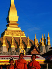L-21-2187-three_young_monks_standing_in_front_of_pha_that_luang__vientiane__vientiane_prefecture__laos-Z00DABWZ.jpg